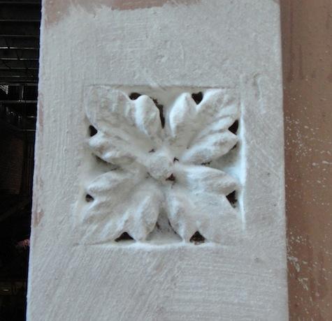 Restoring rosette in brownstone façade
