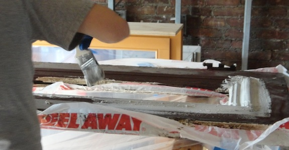 Putting on a thick paste to remove paint from old doors