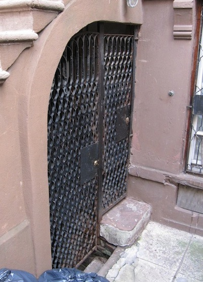 original gates under stoop on Harlem brownstone